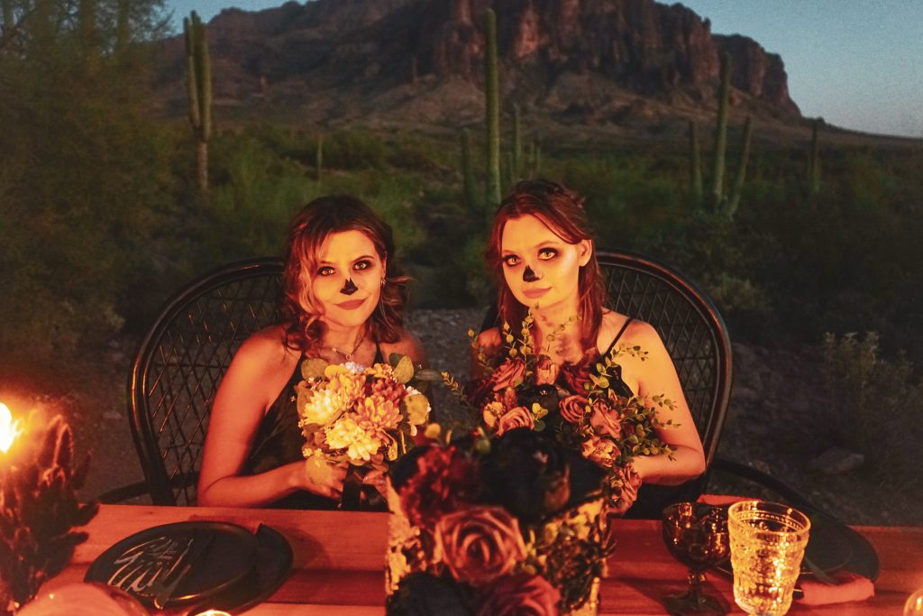 Two models holding floral bouquets for in front of the Superstition Mountains